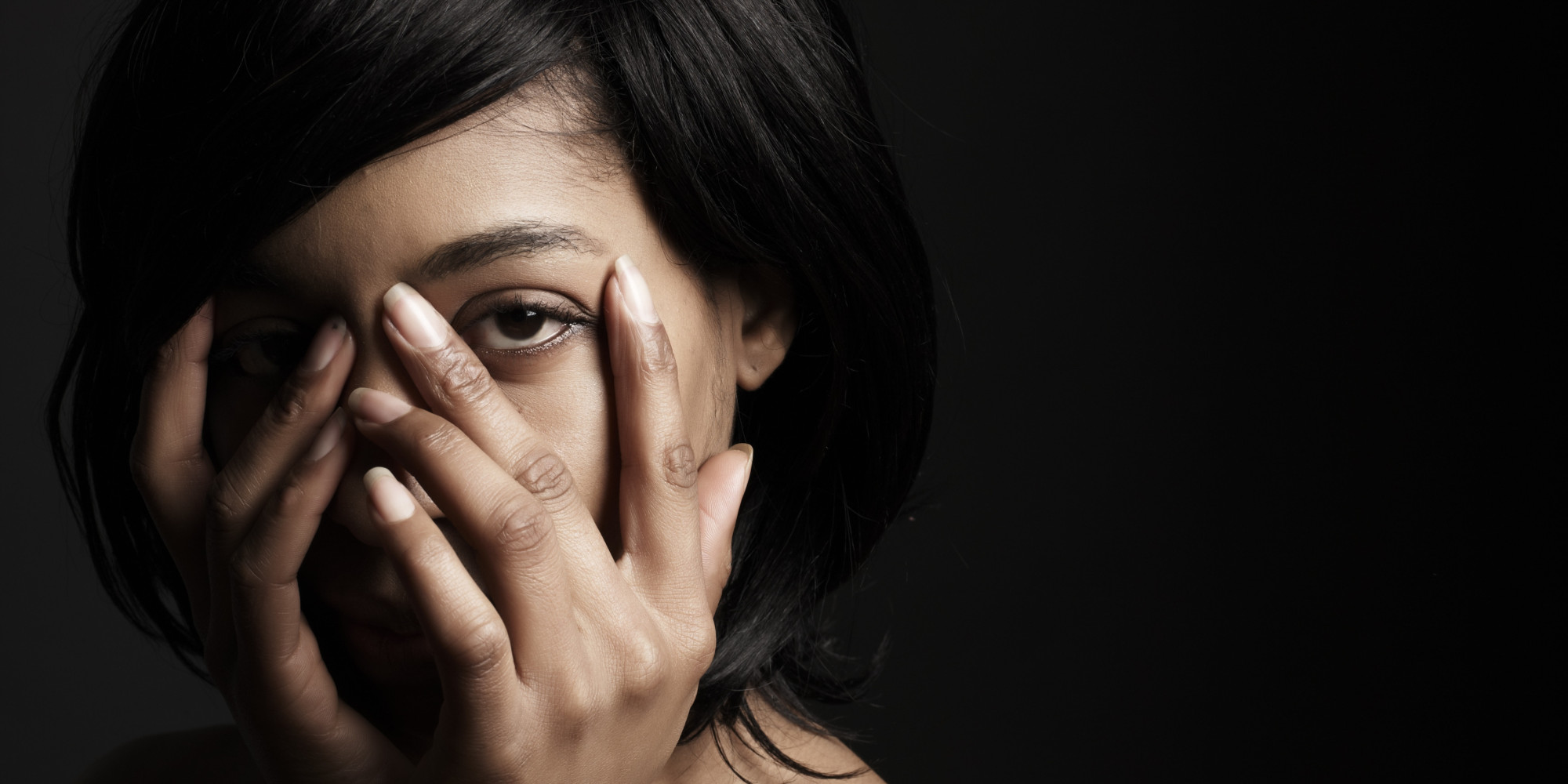 African American woman looking through her hands.